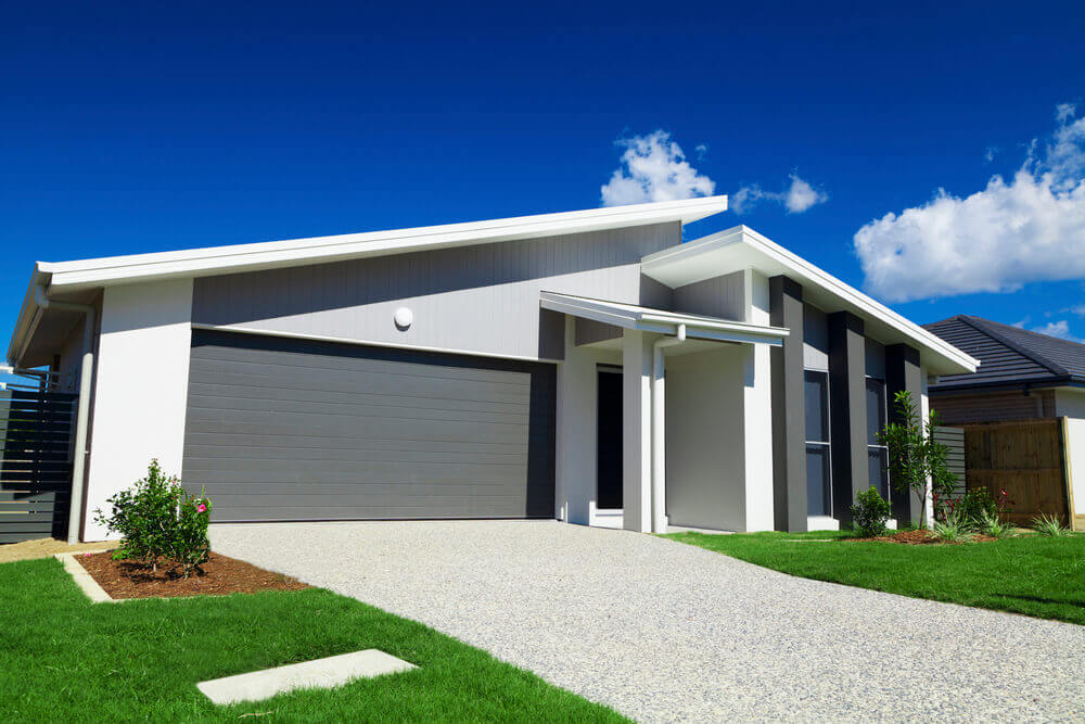 view of the front of a suburban house with green grass and a new concrete driveway poured by concreting Ipswich