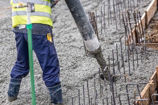 A concreting Ipswich worker guiding a concrete pump hose while standing in wet concrete